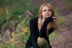 Stilfull mystisk blondin som sitts på gläntan Arkivfoto