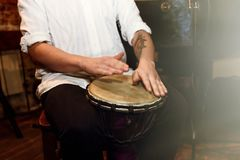 Stilfull percussionist som spelar på lädervalsen på en konsert, hand arkivfoton