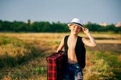 Stilfull pojke med resväskan på den lantliga vägen Arkivfoto