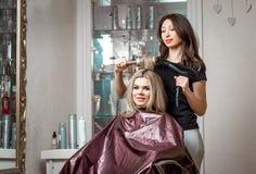 Stilfull professionell, frisör som gör hairdoing till klienten med en hårtork på bakgrunden av frisör`en s royaltyfri foto