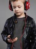 Stilfull pys i hörlurar lyssnande musik för stiligt barn arkivfoton