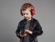 Stilfull pys i hörlurar lyssnande musik för stiligt barn arkivbilder