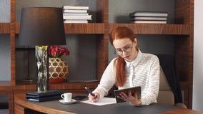 Stilfull rödhårig manflicka som arbetar det hemmastadda kontoret stock video