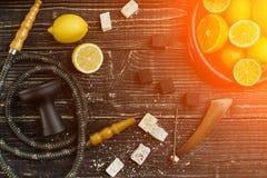 Stilfull röka vattenpipa och korg med citronen, limefrukt och apelsinen på royaltyfri bild