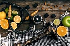 Stilfull röka vattenpipa och korg med citronen, limefrukt och apelsinen på royaltyfria bilder