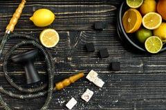 Stilfull röka vattenpipa och korg med citronen, limefrukt och apelsinen på royaltyfria foton