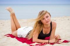 Stilfull sexig flicka i vita jeanskortslutningar Vila på en strand som tycker om solen; frihetssommartidbegrepp Royaltyfri Fotografi
