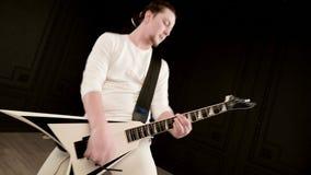 Stilfull solo gitarrist med dreadlocks p? hans huvud och i vit kl?der p? svart spela f?r bakgrund expressively arkivfilmer