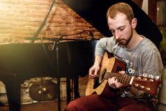 Stilfull solo gitarrist som utför på en konsert på en bakgrundsnolla arkivbilder