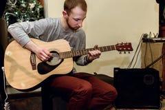 Stilfull solo gitarrist som utför på en konsert på en bakgrundsnolla royaltyfri fotografi
