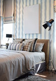 Stilfull sovruminre med randiga kuddar på säng Fotografering för Bildbyråer