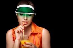 Stilfull sportig kvinna som läppjar ett exponeringsglas av fruktsaft Banta för skönhet Arkivbild