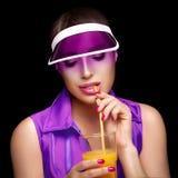 Stilfull sportig kvinna som läppjar ett exponeringsglas av fruktsaft Banta för skönhet royaltyfria foton