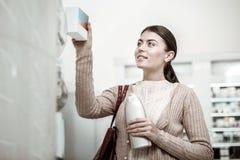 Stilfull stråla kvinna som väljer hennes favorit- objekt på apoteklager royaltyfri bild