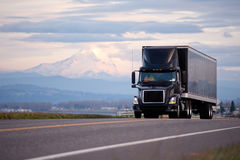 Stilfull svart modern kraftig lastbil med scenisk ro för svart släp Arkivbild