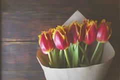 Stilfull tappningbukettsammansättning med bifärgtulpan på trätabellen för mörk brunt Bi-färgade blommor som slås in i papper arkivfoto