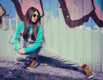 Stilfull tonårs- flicka i färgrik solglasögon som poserar nära grafitti Arkivbild
