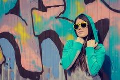 Stilfull tonårs- flicka i färgrik solglasögon som poserar nära grafitti Arkivfoton