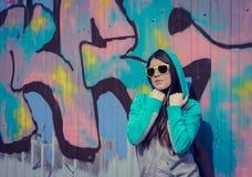 Stilfull tonårs- flicka i färgrik solglasögon som poserar nära grafitti Fotografering för Bildbyråer