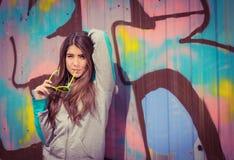Stilfull tonårs- flicka i färgrik solglasögon som poserar nära grafitti Royaltyfri Foto