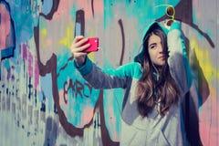 Stilfull tonårs- flicka i färgrik solglasögon som poserar nära grafitti Arkivbilder