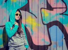 Stilfull tonårs- flicka i färgrik solglasögon som poserar nära grafitti Royaltyfri Bild