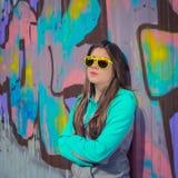 Stilfull tonårs- flicka i färgrik solglasögon som poserar nära grafitti Royaltyfria Bilder