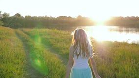 Stilfull tonårs- flicka med kanekalon i hår och band i händer som går på sommaräng nära floden stock video