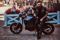 Stilfull trendig cyklist i iklädd solglasögon ett svart läderomslag som sitter på hans specialtillverkade retro motorcykel royaltyfri bild