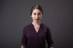 Stilfull ung affärskvinna med ett vänligt uttryck som ser direkt på kameran, closeup av hennes framsida på en grå färg fotografering för bildbyråer