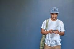Stilfull ung asiatisk man som utanför läser ett textmeddelande Arkivfoton