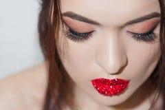Stilfull ung brunett med ljus och stilfull makeup Ögonskugga med pilar och ljusa röda kanter arkivbild