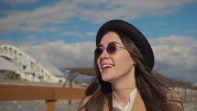 Stilfull ung brunneteflicka som går på stranden lager videofilmer