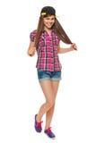 Stilfull ung flicka i ett lock, en skjorta och grov bomullstvillkortslutningar Gatastiltonåring, livsstil som isoleras på vit bak arkivfoto