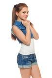 Stilfull ung flicka i jeans väst och grov bomullstvillkortslutningar Gatastiltonåring, livsstil som isoleras på vit bakgrund Fotografering för Bildbyråer