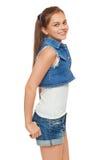 Stilfull ung flicka i jeans väst och grov bomullstvillkortslutningar Gatastiltonåring, livsstil som isoleras på vit bakgrund arkivfoto
