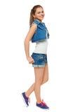 Stilfull ung flicka i jeans väst och grov bomullstvillkortslutningar Gatastiltonåring, livsstil som isoleras på vit bakgrund Arkivbild