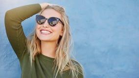 Stilfull ung kvinna, i att le för solglasögon royaltyfri fotografi