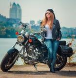 Stilfull ung kvinna i ett läderomslag och jeans i en gla Arkivbild