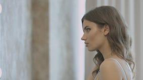 Stilfull ung kvinna i klänningen som framme vrider av spegeln och ser hennes reflexion arkivfilmer