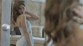Stilfull ung kvinna i klänningen som framme vrider av spegeln och ser hennes reflexion stock video