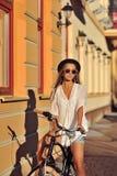 Stilfull ung kvinna på en retro cykel utomhus- stående för mode arkivbilder