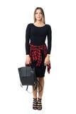 Stilfull ung kvinna som bär den svarta klänningen som bär den svarta läderpåsen som ser kameran Royaltyfria Foton