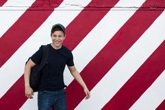 Stilfull ung man på en ljus väggbakgrund Royaltyfri Bild
