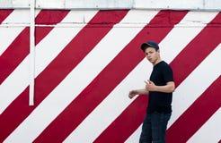 Stilfull ung man på en ljus väggbakgrund Arkivfoton
