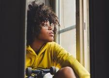 Stilfull ung sinnlig svart eftertänksam kvinna som sitter nära fönstret med en skateboard arkivfoto