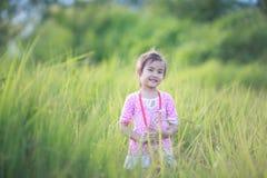 Stilfull ungeflicka som ler i naturbakgrund Fotografering för Bildbyråer