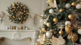 Stilfull vit inre med granjulträd och krans mycket av guld- garneringar, leksaker, ljus och girlander arkivfilmer