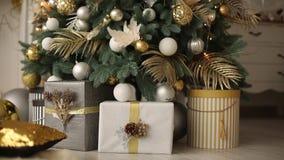 Stilfull vit inre med handgjorda gåvor och gåvor som dekoreras med band och bulor under julgranen stock video