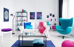 Stilfull vit vardagsrum med färgrik tillbehör, den vita soffan och metallkaffetabellen i mitt bredvid blå äggstol som är verklig royaltyfri bild